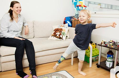 Jesse seisoo lattialla, nauraa ja esittelee sääriproteesiaan. Jessen äiti katsoo häntä sohvalta ja hymyilee.