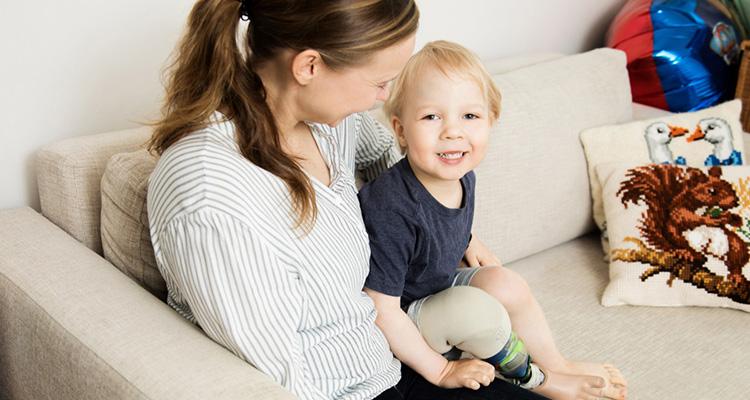 Jesse istuu sohvalla äitinsä sylissä. Jesselle on sääriproteesi.