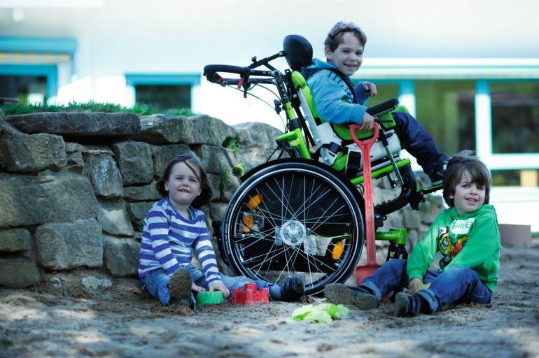 Manuaalisessa pyörätuolissa istuva poika leikkii hiekkalaatikolla kahden muun lapsen kanssa