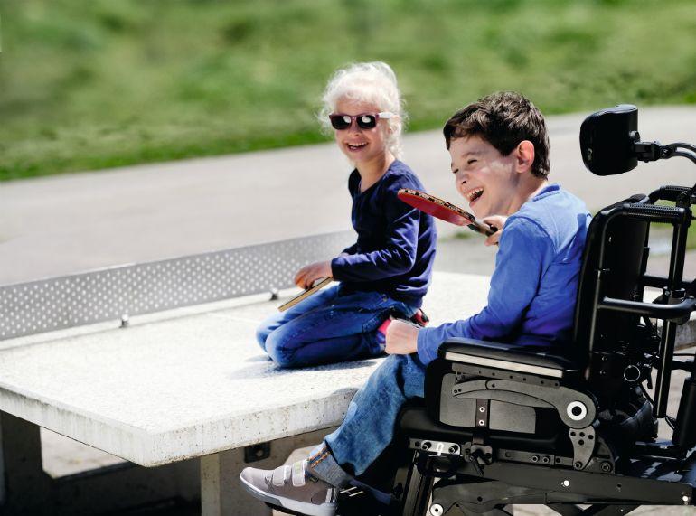 Tyttö ja sähköpyörätuolissa istuva poika nauravat pingismailat kädessä pingispöydän päällä.