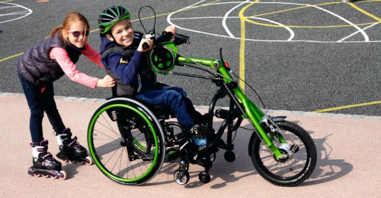 Tyttö ajaa pyörätuoliin liitetyllä käsipyörällä ja vetää toista rullaluistelevaa tyttöä